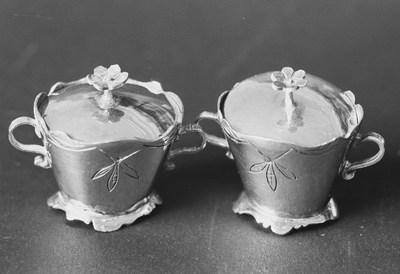Zilveren terrine met deksel in miniatuur. Onderdeel van een stel van twee terrines, de andere is KOG 81-1. De bakjes zijn ovaal en omgekeerd conisch van vorm met een geaccouleerde rand en twee s-vormige staande oren. Langs de rand is een bladmotief gegraveerd. De licht gewelfde voet heeft een geaccouleerde rand. Het deksel is licht gewelfd met een zesbladige bloem op een staande steel als knopje.