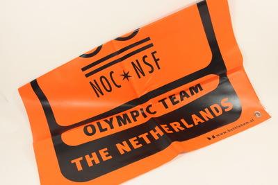 Een rechthoekig oranje spandoek met zwarte opdruk van de Olympische Winterspelen 2002; bovenaan staat de inscriptie 'SALT LAKE 2002' met daaronder de Olympische Ringen en de inscriptie 'NOC*NSF / OLYMPIC TEAM / THE NETHERLANDS'