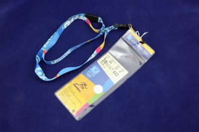 Toegangsbewijs van de atletiek wedstrijd; bovenaan een wit vlak met de inscriptie eerst in het Grieks en daarna in het Engels 'Gate Aisle Row Seat / 9 109 32 9 / 28 August 2004 612 / 20:00'; de achtergrond van het toegangsbewijs onder de witte balk is opgedeeld in rechthoekige gekleurde vlakken in de kleuren blauw, oranje en geel; in het blauwe vlak staat het logo van de Olympische Zomerspelen 2004, in het oranje vlak staat een hardlopende pictogram; de kaart zit in een plastic hoesje dat aan een keycoard hangt.
