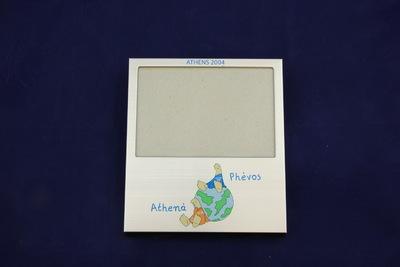 Een grijs fotolijstje met bovenaan de blauwe opdruk 'ATHENS 2004' daaronder een ruimte van 9 x 13,5 cm voor een liggende foto en daaronder een wereldbol met daaop Phevós en daarnaast Athenà (de mascottes van de Olympische Zomerspelen 2004).
