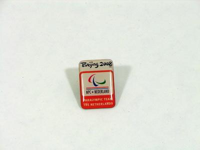 Reversspeld van het Paralympische team van de Zomerspelen Beijing 2008. Vierkante reversspeld met als opschriften: Beijing 2008 / (embleem PS 2008) / NPC * NEDERLAND / PARALYMPISCH TEAM / THE NETHERLANDS.