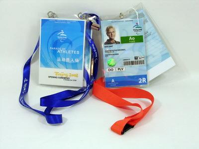 Driedelige Identiteitskaart Rian Smit, NOC*MSF met oranje sleutelkoord van het Paralympische team van de Zomerspelen Beijing 2008. Opschriften o.a: Beijing 2008 Paralympics / (pasfoto) Rian Smit / Administrative personnel/ The Netherlands. Aan hetzelfde slutelkoord zit ook een gelijke grootte 'Upgrade card' voor o.a. 'Paralympic family' en een NOC*NSF-kaart. Bij het sleutelkoord met identiteitskaart behoren nog twee 'tickets' voor de openings- en sluitingsceremonie van de spelen met elk 'Beijing 2008' donkerblauw sleutelkoord (7b en 7c).