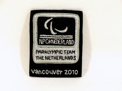 Applicatie Nederlands Paralympisch team 2010 Vancouver. Zwart viltenondergrond met in zilverdraad embleem NPC. Opschriften: (logo NPC) / NPC*NEDERLAND / PARALYMPIC TEAM / THE NETHERLANDS / VANCOUVER 2010.