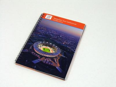 Een boek bestaande uit 84 pagina's met daarin de Nederlandse deelnemers van de Paralympische Zomerspelen 2012; op de kaft staat een foto van het Olympisch Stadion in Londen; op de voorkant staat aan de bovenkant de titel 'Teamboek / Paralympic Team Netherlands / London 2012'. Met zwart metalen ringband.