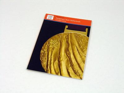 Een boek bestaande uit 30 pagina's met daarin informatie over de Paralympische Zomerspelen 2012; op de kaft staat een foto van een gouden Paralympische medaille van London 2012; aan de bovenkant van de kaft de titel 'Informatieve gids / Paralympic Team Netherlands / London 2012'.