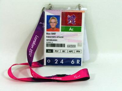Identiteitskaarten van Rian Smit (NOC*NSF voor de Paralympische Zomerspelen 2012 Londen. De identiteitskaart voor de Paralympische Zomerspelen 2012 Londen heeft paars/roze sleutelkoord met bijgevoegd uitbreidingskaart 'Proxy card'. Tevens aan oranje sleutelkoord een NOC*NSF identiteitskaart' (C2012PZ-3b) en een los sleutelkoord in groen met 'Chef de Mission' (C2012PZ-3c).