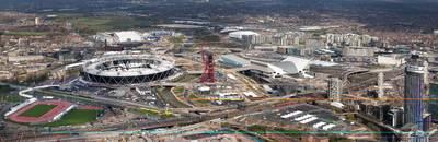Panorama poster van het Olympisch park van de Olympische Zomerspelen 2012 London in april 2012. Links het Olympisch Stadion en op de voorgrond het Olympisch treinstation en in het midden de uitkijktoren. De sportaccomedaties lijken allemaal gereed, maar er wordt nog druk gewerkt aan de transportinfrastructuur; wegen treinverbinding en bruggen etc. Rechtsonder de twee logo's van Olympische en Paralympische Spelen van London 2012 en de titel 'Aerial view of the Olympic Park site - April 2012'.