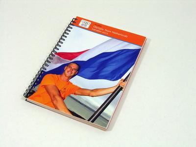 Een boek bestaande uit 145 pagina's met daarin de Nederlandse deelnemers van de Olympische Zomerspelen 2012; op de kaft staat een foto van windsurfer Dorian van Rijsselberghe; op de voorkant staat aan de bovenkant de titel 'Teamboek / Olympic Team Netherlands / London 2012'. Met zwart metalen ringband.