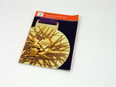 Een boek bestaande uit 30 pagina's met daarin informatie over de Olympische Zomerspelen 2012; op de kaft staat een foto van een gouden Olympische medaille van London 2012; aan de bovenkant van de kaft de titel 'Informatieboek / Olympic Team Netherlands / London 2012'.