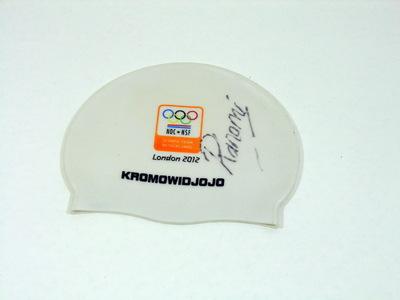 Badmuts Nederlands Olympisch Team London 2012 met handtekening van Ranomi Kromowidjojo. Witte badmuts van plastic met aan een kant het logo van het Nederlands Olympisch Team met eronder London 2012 met rechts daarvan een handtekening Ranomi. De muts is op het sportgala van NOC*NSF op 3 november 2012 op de goeden doelenveiling door NOC*NSF zelf gekocht als aanwinst voor de collectie. Ranomi was op de Olympische Zomerspelen in Londen één van de succesvolste Olympiers van Nederland. Op de spelen behaalde zij achter Australië een zilveren plak op de 4 x 100m vrije slag. De andere leden van haar estafetteploeg waren Inge Dekker, Marleen Veldhuis en Femke Heemskerk. Kromowidjojo startte als laatste. Haar splittijd van 51,93 seconden was de snelste ooit op een dergelijke estafette. Zij was zeventiende seconde sneller dan de nummer twee van het veld. In Londen wist zij een gouden medaille te behalen op de 100 meter vrije slag met een olympisch record van 53,00 seconden. Zij won later ook de 50 meter vrije slag in een olympische recordtijd van 24,05 seconden. Trainingsmaatje Marleen Veldhuis won brons. Na Kristin Otto, Inge de Bruijn en Britta Steffen is Kromowidjojo de vierde zwemster die op een en dezelfde Olympische Spelen zowel op de 50 als op de 100 meter vrije slag goud behaalde sinds de introductie van de 50 meter vrije slag op de Olympische Spelen van 1988. De Europese zwembond LEN riep haar vervolgens uit tot Europees zwemster van het jaar 2012. In december 2012 werd Kromowidjojo evenals in 2011 verkozen tot Sportvrouw van het jaar tijdens het Sportgala.