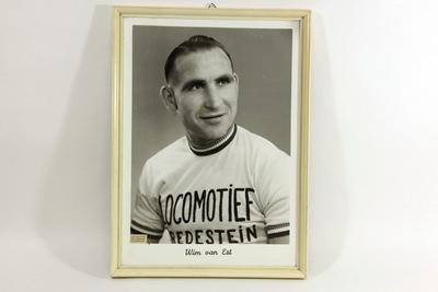 Een portret zwart/wit foto van Wim van Est. Wim draagt een wit T-shirt met op de borst de zwarte inscriptie 'LOCOMOTIEF / REDESTEIN'. Een van zijn bijnamen was 'de locomotief'. Hij heeft zijn hoofd licht naar links gedraaid waardoor hij driekwart aangezicht heeft. De foto zit in een witte passé partout met onderaan de inscriptie 'Wim van Est'. Wim van Est (Fijnaart, 25 maart 1923 - Roosendaal, 1 mei 2003[1]) was een Nederlands wielrenner, en de eerste Nederlander die in de Tour de France de gele trui droeg als leider van het algemeen klassement. Bijnamen van Wim van Est waren: De Locomotief, IJzeren Willem, de Knoest en de Beul van het Heike.