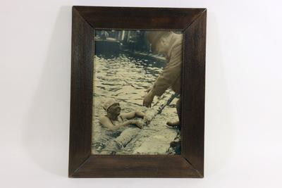 Een ingelijste zwart/wit foto van Truus Klapwijk. De zwemster bevindt zich in het water en houdt zich vast aan de rand van het zwembad met beide handen. Ze draagt een witte badmuts en kijkt omhoog naar haar vader. Haar vader staat op de rand van het zwembad en buigt door de knieën met uitgestrekte armen. Hij draagt een bruine jas met hoed. Op de achterzijde van de lijst staat rechts onderaan de handgeschreven inscriptie 'Truus Klopwijk / met haar vader'. Geertruida (Truus) Klapwijk (Rotterdam, 2 januari 1904 – aldaar, 3 mei 1991) was een topzwemster, die Nederland tweemaal vertegenwoordigde bij de Olympische Spelen: 'Parijs 1924' en 'Amsterdam 1928'.