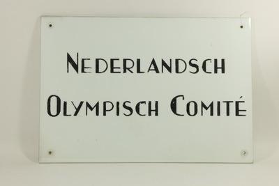 Wit marmeren gevelbord Nederlandsch Olympisch Comité. Bord heeft op elk van de hoeken een gat voor montage aan gevel. In 1993 ging het NOC samen met het NSF.