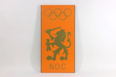 Een oranje bord met daarop het logo van het Nederlands Olympisch Comité. Bovenaan staan de goudkleurige Olympische Ringen met daaronder het wapen van de Nederland, de leeuw. Onderaan staat goudkleurig 'N.O.C.'.