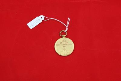 Een goudkleurige medaille. Op de voorzijde is een relief van een dame die van een duikplank afspringt. Ze heeft haar armen achter zich. In de achtergrond zijn enkele andere badgasten te zien aan de rand van het zwembad. Op de achterzijde staat de inscriptie 'H.P.C. / 23.4.44 / SCHOONSPRINGEN / 1e P.'.