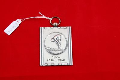 Een zilverkleurige rechthoekige medaille met een relief van een schoonspringer. Hij is in het midden van zijn sprong en heeft gestrekte benen. Hij is voorover gebogen en heeft zijn handen op zijn voeten. Onderaan is het water van het bad te zien. Onderaan staat de inscriptie '1e PR. / 25 Oct.1942'.
