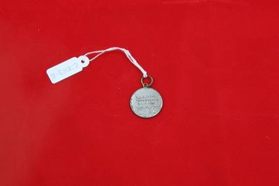 Een zilverkleurige medaille met twee zwemmers die aan het borstcrawlen zijn op de voorzijde. Op de achterzijde staat de inscriptie 'A.O.Z. 1e PR. / SCHOONSPR. D. / 5-2-'46'.