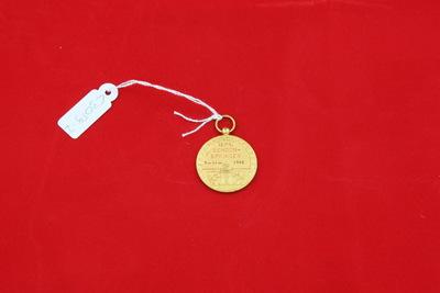 Een goudkleurige medaille met in het midden een vlag met daarop de letter 'Y'. In de achtergrond is een reddingsboei te zien met daarop de inscriptie 'ZWEMVERENIGING / HET Y'. Op de achterzijde staat de inscriptie '1e PR. / SCHOON- / SPRINGEN / 7-11-1942'. Onder de inscriptie is het stadswapen van Amsterdam te zien.