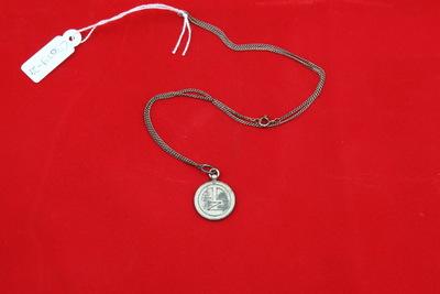 Een zilverkleurige hanger aan een ketting met op de voorzijde de inscriptie 'AD / Z'. Op de achterzijde staat de inscriptie 'DEMONSTRATIE / 18-6-'40 / SCHOONSPRINGEN'.