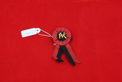 Een rozet in de kleuren zwart/rood met in het midden een goudkleurig anagram van de letters 'KV'. Onder het rozet zitten nog twee lintjes in dezelfde kleuren.