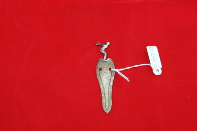 Een zilverkleurige papierclip met boven op een zwemmer, die in de startpositie staat om te springen. Zijn armen gestrekt achter zijn rug en zijn benen licht gebogen. Onder de figuur staat de inscriptie 'R.Z.C. / SCHOONSPR. D / 1e PR / 12-3-44'.