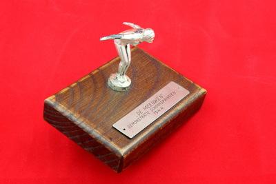 Een sportprijs bestaande uit een houten sokkel, waarop een zilverkleurig figuur is bevestigd. De figuur staat in start positie van een sprong. Ze heeft haar armen gestrekt achter haar rug en haar benen licht gebogen. Ze draagt een zwempak met badmuts. Onderaan is een metalen plaatje bevestigd met de inscriptie 'DE MEEUWEN/ DEMONSTRATIE SCHOONSPRINGEN / 1944'.