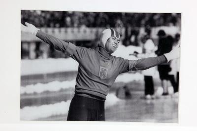 Een zwart/wit ingelijste foto van Stien Kaiser op de Olympische Winterspelen 1972 Sapporo. Stien heeft net gefinisht op de 3000m en heeft goud behaald. Ze heeft beide handen in triomf in de lucht. Ze is gefotografeerd vanaf haar heupen.