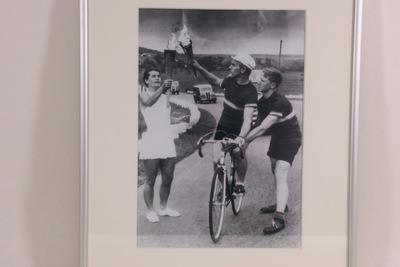 Een zwart-wit foto van fakkeltocht van de Olympische Zomerspelen 1952 Helsinki. Op de foto wordt het vuur overgedragen van een hardloopster aan een wielrenner. De twee sporters houden de fakkels bij elkaar en het vuur wordt aangestoken. De wielrenner's fiets wordt vastgehouden door een tweede persoon.