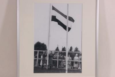 Een zwart-wit foto van twee soldaten die een Nederlandse vlag aan het hijsen zijn. Achter het hekwerk staan verschillende toeschouwers. Op de achterzijde van de lijst staat de handgeschreven inscriptie '1952 / Zomerspelen'.