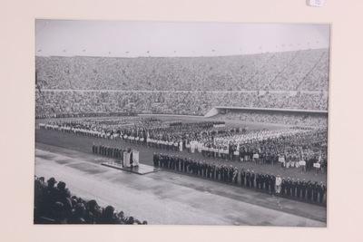 Een zwart/wit foto van de openingsceremonie van de Olympische Zomerspelen 1952 Helsinki. Op het middenveld staan de verschillende deelenemende landen opgesteld. Het stadion zit vol met publiek.