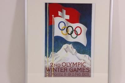 De Winterspelen in St.-Moritz, Zwitserland, waren de eerste die gehouden werden in een ander land dan dat waar de Zomerspelen in hetzelfde jaar plaatsvonden. De toppen van de Corvatch Spiz (Grison bergen) domineren de poster van de Olympische Winterspelen in St. Mortiz. Daar boven wapperen de vlaggen van Zwitserland en van het international Olympische Comité. Onderaan de poster staat de inscriptie '2nd OLYMPIC / WINTER GAMES / St. Moritz 11.-19.th Febr.1928'.