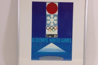Een kleurenposter van de Olympische Winterspelen 1972 Sapporo. Een blauwe poster met in het midden bovenaan de rode rijzende zon van Japan, in het midden het logo van de Spelen 1972 en daaronder de gekleurde Olympische Ringen met de grijze inscriptie 'SAPPORO '72'. Onderaan staat de blauwe inscriptie 'XI OLYMPIC WINTER GAMES'. De Japanse Sapporo Spelen in 1972 waren de eerste die plaatsvonden buiten Europa of de USA. Verscheidene bekende Japanse ontwerpers waren betrokken bij het ontwerp van de posters. Vier werden er geselecteerd.