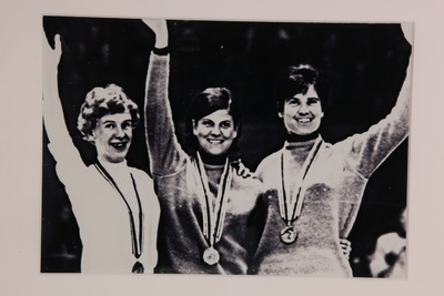 Een ingelijste zwart/wit foto van Mustenen, Ans Schut en Stien Kaiser op het podium van de Olympische Winterspelen 1968 Grenoble. De dames hebben alle hun medaille om hun nek hangen en zwaaien lachend naar het publiek.