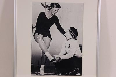 Een ingelijste zwart/wit foto van Sjoukje Dijkstra en Carol Heiss Jenkins. Carol Heiss Jenkins zit op haar knieën en helpt Sjoukje Dijkstra haar schaatsen aan te trekken. Sjoukje leunt met haar linkerhand op de rechterschouder van Carol.