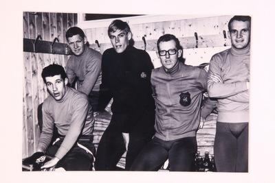 Een ingelijste zwart/wit van het schaatsteam mannen op de Olympische Winterspelen 1972 Sapporo. De foto toont Ard Schenk, Kees Verkerk, Jan Bols, Peter Nottet. De schaatsers zitten in een soort van kleedkamer in hun trainingstenue.