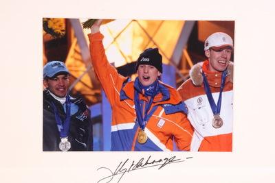 Een ingelijste kleurenfoto van Jochem Uytdehaage op het podium van de Olympische Winterspelen 2002 Salt Lake City. Links van hem staat de zilveren medaille winnaar Derek Parra en rechts de bronzen Jens Boden. De drie dragen allen hun medaille en lachen en zwaaien naar het publiek. Op de witte passe-partout staat onderaan de handtekening van Uytdehaage.