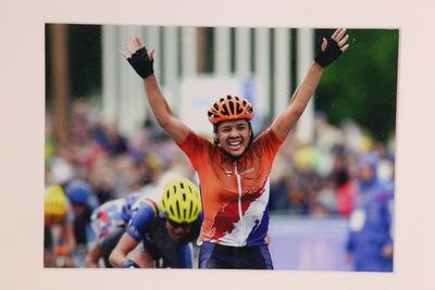 Een ingelijste foto van Van Moorsel op de Olympische Zomerspelen 2000 Sydney. Leontien is net gefinisht op de wegwedstrijd en heeft goud behaald. Ze is gefotograveerd vanaf haar middel en ze heeft haar handen in triomf de lucht ingestoken