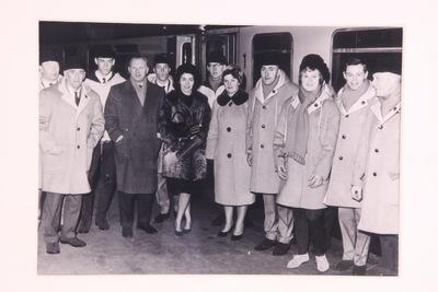 Een ingelijste zwart/wit foto van de gehele schaatsploeg van de Olympische Winterspelen 1964 Innsbruck. De ploeg staat voor de trein op centraal station Amsterdam voor hun vertrek naar de Olympische Winterspelen op 21-01-1964.