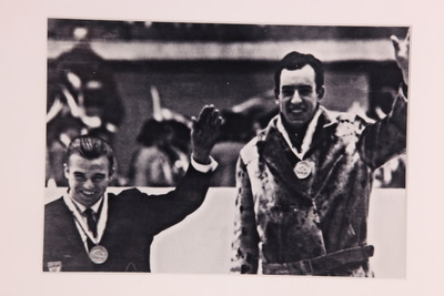 Een ingelijste zwart/wit foto van Kees Verkerk en Ants Antson op het podium van de Olympische Winterspelen 1964 Innsbruck. Beide mannen lachen en zwaaien met hun rechterhand.