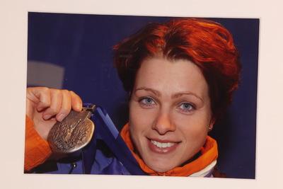 Een ingelijste kleurenfoto van Gretha Smit op de Olympische Spelen 2002 Salt Lake City. Rechts in het beeld is het portret van Gretha, met kort rood haar en blauwe ogen. Om haar hals draagt ze een zilveren medaille die ze met haar rechterhand naast haar gezicht houdt. Gretha Smit haalde op de 5.000 meter lange baan een zilveren medaille.