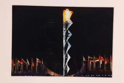 Een ingelijste kleurenfoto van de toren met Olympische vuur op de Olympische Spelen 2002 Salt Lake City. De toren staat in het midden en links en rechts daarvan staan vlaggenmasten met de vlaggen van de deelnemende landen.