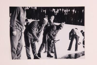 Een zwart/wit ingelijste foto een Italiaans team die aan het ijszagen zijn op de Olympische Winterspelen 1956 Cortina d'Ampezzo.