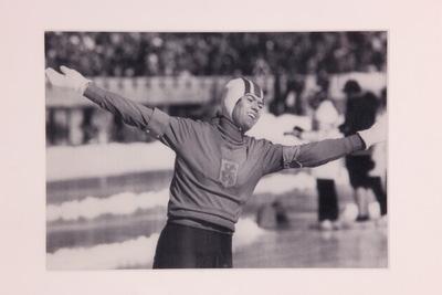 Een zwart/wit ingelijste foto van Stien Kaiser op de Olympische Winterspelen 1972 Sapporo. Stien is net gefinisht op de 3000m en heeft goud behaald. Ze heeft beide handen in triomf in de lucht. Ze is gefotografeerd vanaf haar heupen.