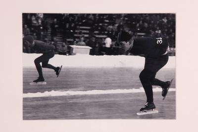 Een zwart/wit ingelijste foto van twee lange baan schaatser (misschien Jan Pelsman?). De voorste schaatser heeft het cijfer 32 op zijn linkerarm.