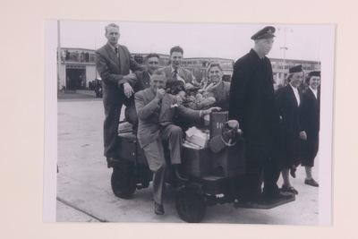 Een zwart/wit foto van enkele Nederlandse deelnemers op de Olympische Zomerspelen 1952 Hesinki. De 5 deelnemers zitten op een motor aangevoerd karretje, die wordt bestuurd door een man die voorop staat. In het midden van de wagen staat een bloemstuk.