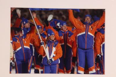 Een kleurenfoto van de Nederlandse deelnemers gedurende de openingsceremonie van de Olympische Winterspelen 2002 Salt Lake. Vooraan loopt de vlaggendrager dit is Nicolien Sauerbreij, een snowboardster.