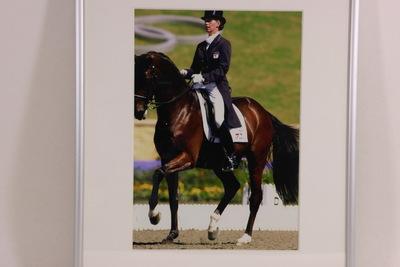 Een kleurenfoto van Anky van Grunsven die op haar paard, Bonfire, haar proef rijdt gedurende de Olympische Spelen 2000 Sydney. Anky draagt haar dressuur tenue, haar blonde haar in een knotje en een hoge zwarte hoed.