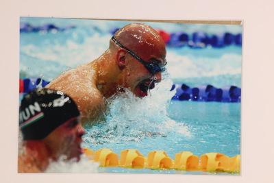 Een kleurenfoto van Marcel Wouda in actie tijdens de mannenestafette op de Olympische Zomerspelen 2000 Sydney. In de achtergrond zie je Marcel omhoogkomen om adem te happen. Hij draagt enkel een duikbrilletje. In de linker beneden hoek zie je een zwemmer in de baan voor hem die eveneens omhoog komt om adem te happen. Deze draagt een zwarte badmuts.