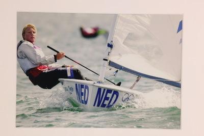 Een kleurenfoto van Margriet Matthijsse in actie tijdens de mannenestafette op de Olympische Zomerspelen 2000 Sydney. Ze zit in een Europe klasser, dit is een eenpersoonszeilboot. Ze hangt links buiten de boot en haar zeil hangt rechts. Op de punt van de boot staat in het blauw de inscriptie 'NED'.