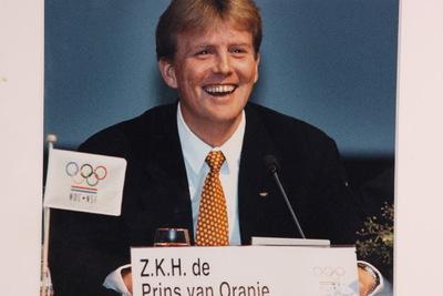 Een kleurenfoto van Willem Alexander tijdens een persconferentie. De prins van Oranje zit lachend achter de microfoon in pak. Hij draagt een rode stropdas met gele stippen. Voor zijn microfoon staat een bordje met de inscriptie 'Z.K.H. de Prins van Oranje'. Links van de prins staat een vlaggetje van NOC*NSF.